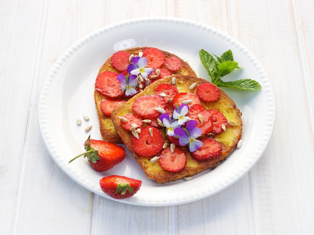 French toast and strawberries, garnished with mint and violas